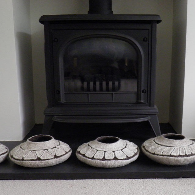 Felt pots sitting in front of a fireplace - FFelted